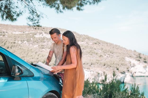 Молодая пара с картой путешествует на машине Premium Фотографии