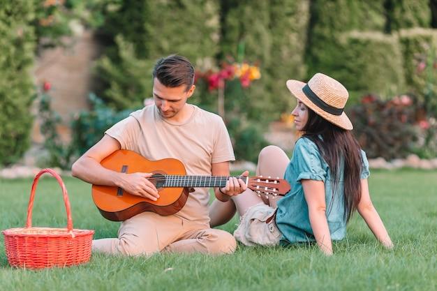 Молодая пара играет на гитаре на траве Premium Фотографии