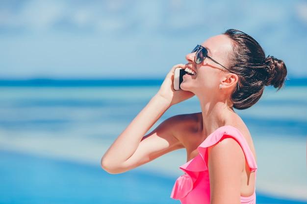 白いビーチに電話で話している若い美しい女性 Premium写真