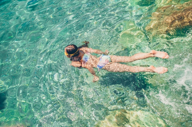 シュノーケリングマスクでの幸せな女の子熱帯魚と水中ダイビング Premium写真