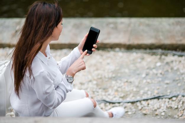 女性の手のクローズアップは路上屋外携帯電話を保持しています。モバイルのスマートフォンを使用している人。 Premium写真
