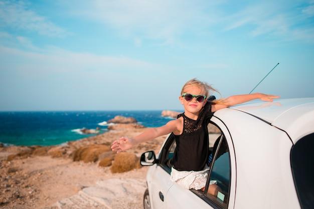 バカンスの小さな女の子が車で旅行します。美しい風景 Premium写真
