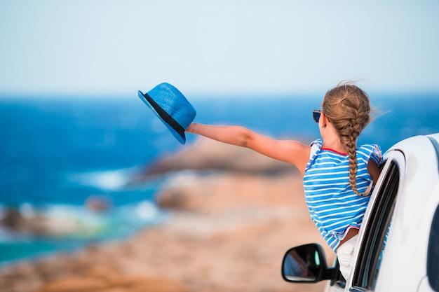 休暇の女の子が美しい景色を車で旅行します。 Premium写真