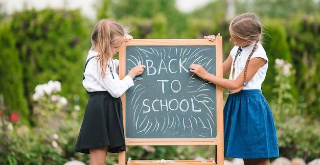 屋外の黒板で幸せな小さな女子学生 Premium写真