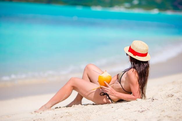 ビーチで暑い日にココナッツミルクを飲む若い女性。 Premium写真
