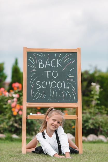 屋外の黒板で幸せな小さな女子高生 Premium写真