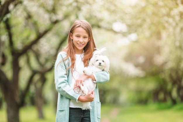 Маленькая улыбающаяся девочка играет и обнимает щенка в парке Premium Фотографии
