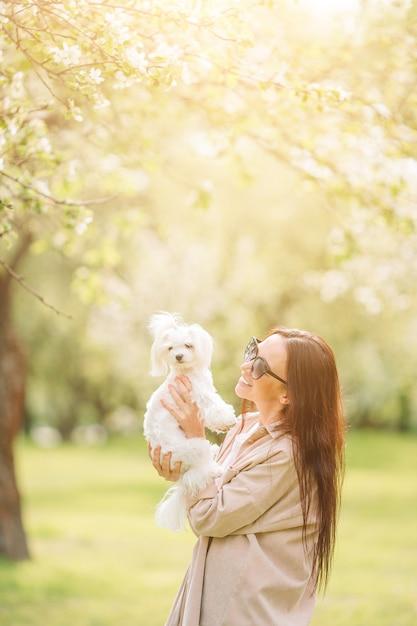 Женщина играет и обнимает щенка в парке Premium Фотографии