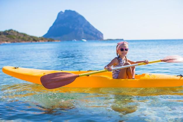 澄んだ青い海でカヤックをする勇敢なかわいい女の子 Premium写真