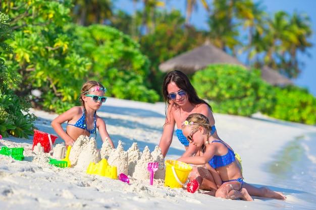 小さな女の子と夏休みにビーチおもちゃで遊んで幸せな母 Premium写真