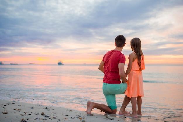 エキゾチックなビーチで夕日を見ている彼の小さな子供を持つ若い父親 Premium写真
