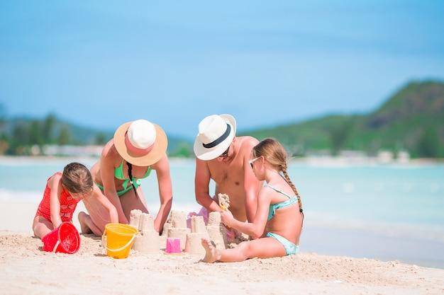熱帯の白いビーチで家族を作る砂の城 Premium写真