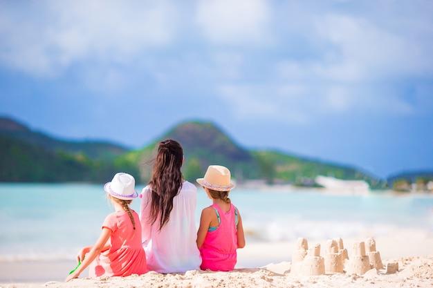 ママと熱帯のビーチで砂の城を持つ子供たちの家族 Premium写真