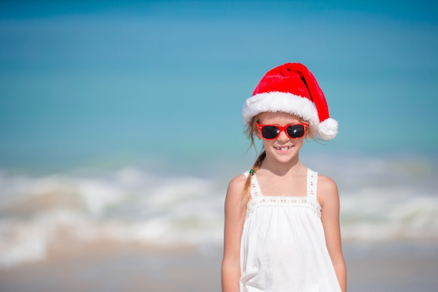 熱帯のビーチのサンタ帽子のかわいい女の子 Premium写真