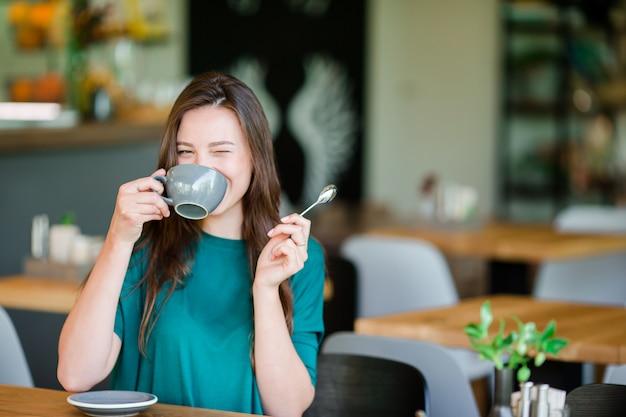 Женщина насладиться вкусным кофе, имея завтрак в кафе на открытом воздухе. счастливая молодая городская женщина пьет кофе Premium Фотографии