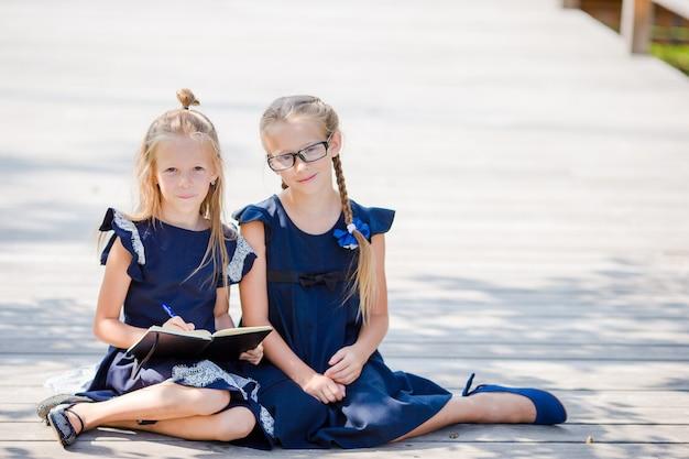 Прелестные маленькие школьницы с примечаниями и карандашами напольными. обратно в школу. Premium Фотографии