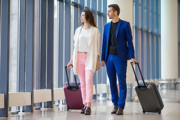 Туристы пара с багажом в международном аэропорту. Premium Фотографии