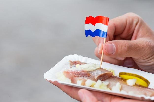 アムステルダムの水路にタマネギとオランダの国旗のおいしい新鮮なニシン。伝統的なオランダ料理 Premium写真