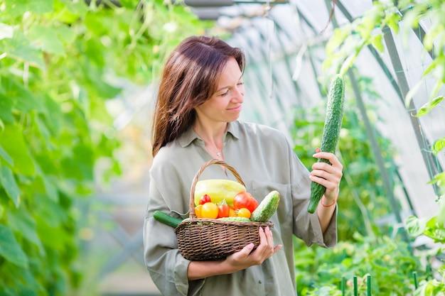 Молодая женщина с корзиной зелени и овощей в теплице. время сбора урожая Premium Фотографии