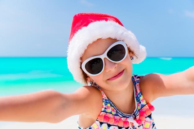 クリスマスのビーチでの休暇中にサンタの帽子のかわいい女の子 Premium写真