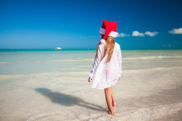 ビーチで赤い帽子サンタクロースでかわいい女の子 Premium写真