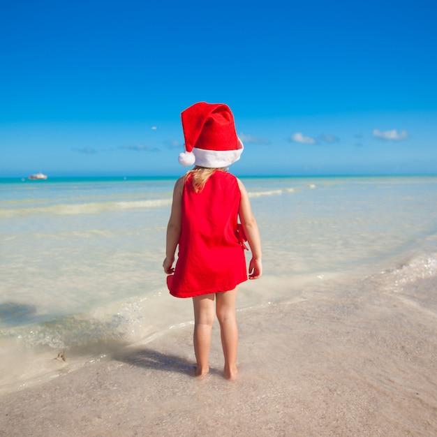 ビーチで赤い帽子サンタクロースでかわいい女の子の背面図 Premium写真