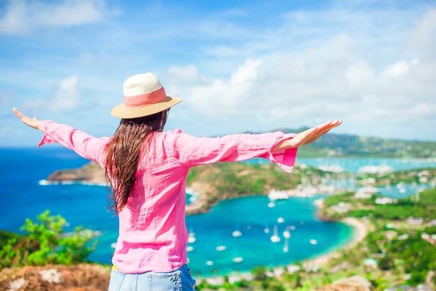 シャーリーハイツ、アンティグア、カリブ海の熱帯の島の楽園湾から英語港の景色を持つ若い観光客女性 Premium写真