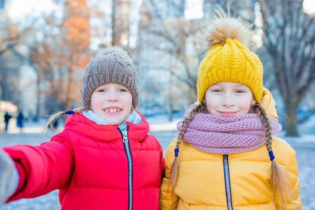 Восхитительные маленькие девочки, делающие фотографию селфи в центральном парке в нью-йорке Premium Фотографии