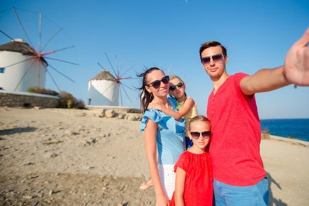 Семья, принимая селфи с палкой перед ветряными мельницами в популярном туристическом районе на острове миконос, греция Premium Фотографии