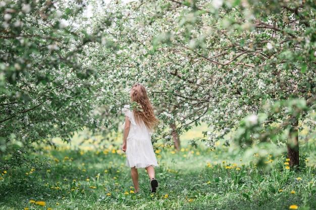 美しい春の日に咲くアップルガーデンでのかわいい女の子 Premium写真