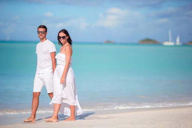 アンティグア島で白い砂浜とターコイズブルーの海の水と熱帯のカーライル湾ビーチを歩く若いカップル Premium写真
