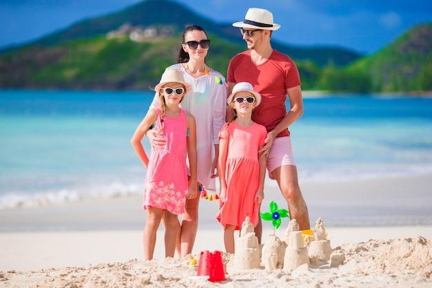 Счастливая красивая семья на тропическом пляже Premium Фотографии