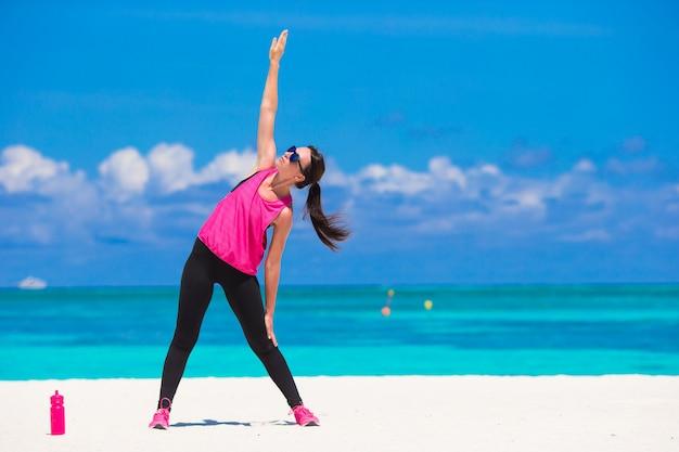 彼女のスポーツウェアの熱帯白いビーチでのエクササイズフィットの若い女性 Premium写真
