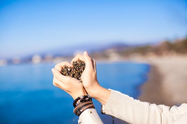 Женщина руки, держа маленькие камни формы сердца Premium Фотографии