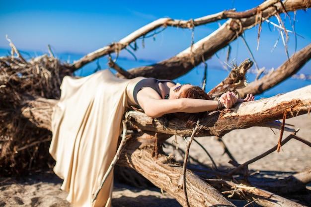 ビーチでポーズをとって長く美しいドレスの魅力的な若い女性 Premium写真