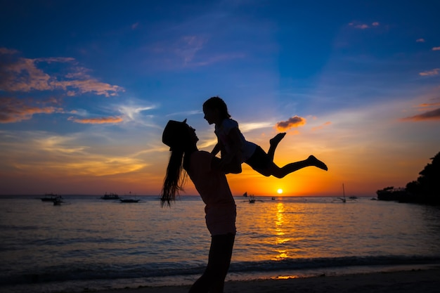 小さな女の子と彼女の母親は、ボラカイ島、フィリピンの日没で楽しんで Premium写真