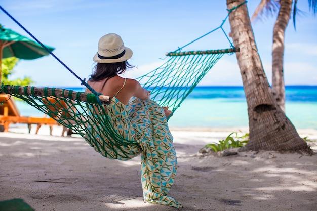 熱帯のビーチでハンモックで横になっている若い女性 Premium写真
