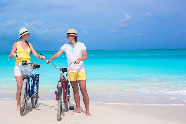夏のビーチでの休暇に自転車で若い幸せなカップル Premium写真