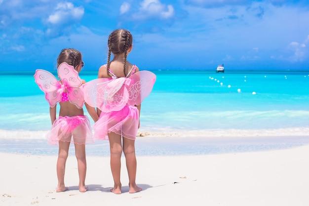 ビーチ夏休みに蝶の羽を持つ少女 Premium写真