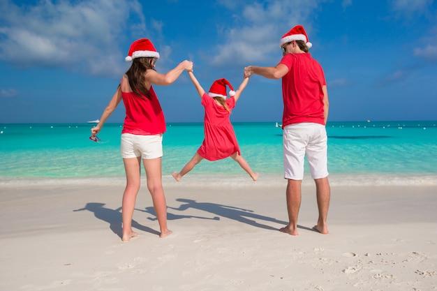 Счастливая семья в рождественские шляпы, развлекаясь на белом пляже Premium Фотографии