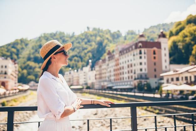 ヨーロッパの都市の山川の堤防に帽子で幸せな女の子。 Premium写真