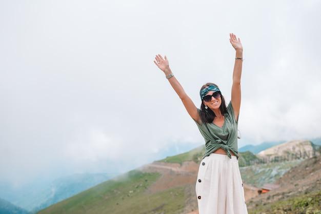 霧の背景の山の美しい幸せな若い女性 Premium写真