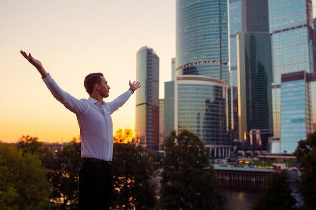ガラスの超高層ビルに対して立ちながらコピースペースを探しているビジネスマンの背面図 Premium写真