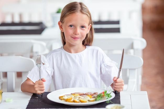 屋外カフェで夕食を食べているかわいい女の子 Premium写真