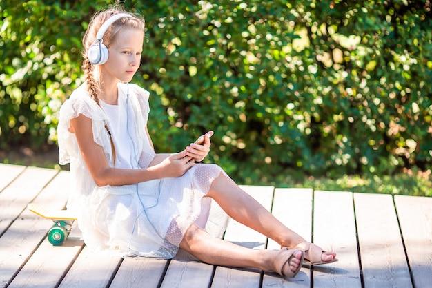 公園で音楽を聴く愛らしい少女 Premium写真