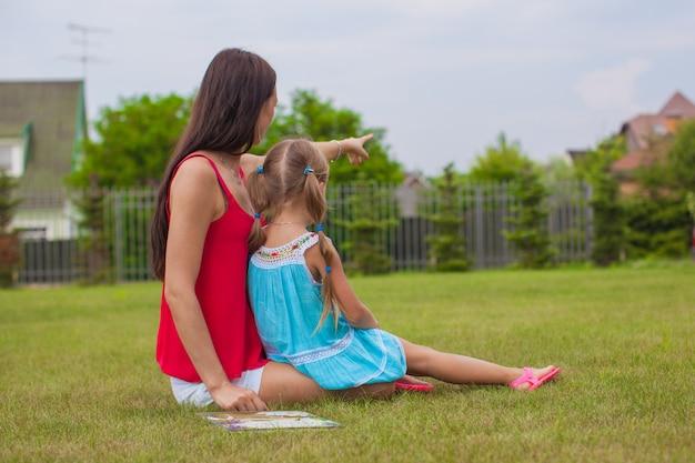 若い母親と家の近くの芝生で休日を楽しんでいるかわいい娘 Premium写真