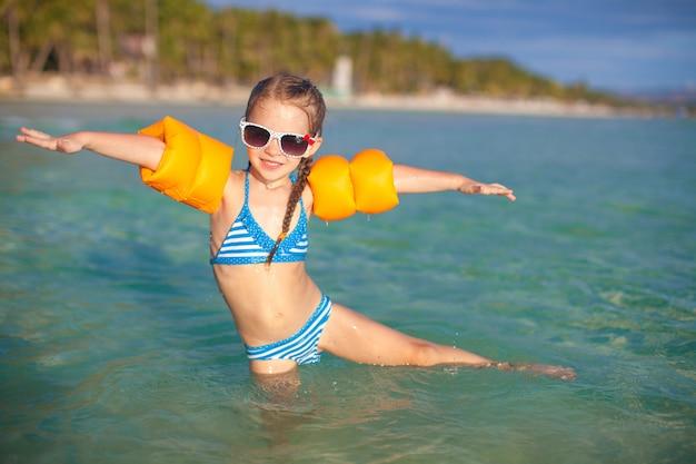 愛らしい少女は、熱帯のビーチでの休暇に海で楽しい時を過す Premium写真