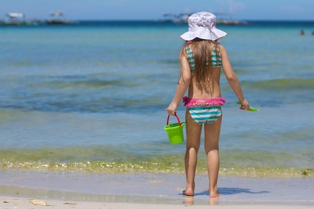 熱帯で歩く美しい水着のかわいい女の子 Premium写真