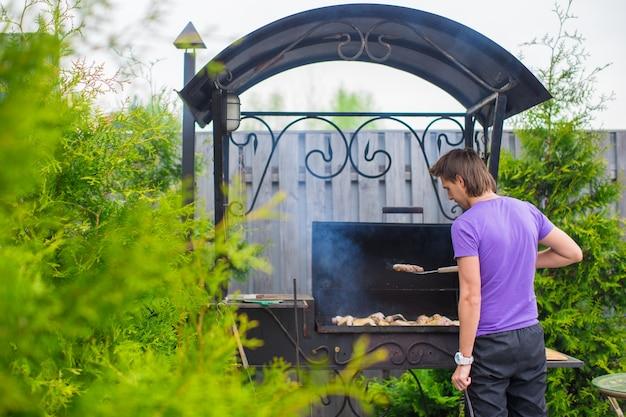 若い男は彼の庭で屋外グリルステーキをフライドポテトします。 Premium写真