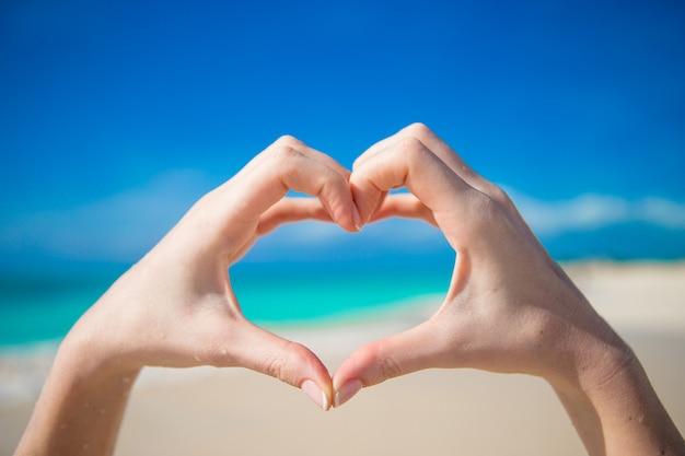 Сердце, сделанное руками фон бирюзовый океан Premium Фотографии